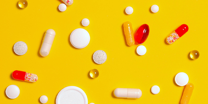 vitamin tablets and capsules on a yellow background