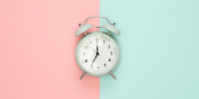 analogue alarm clock on a pink and blue background