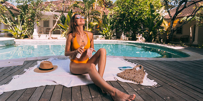 woman in orange bikini applying sunscreen to her hands while sunbathing on a blanket spread on a wooden deck by a pool